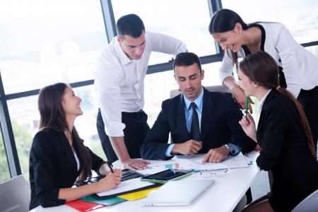 オフィスでの会合で幸せな若いビジネス人々 のグループ