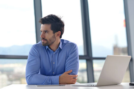 happy young business  man work in modern office on computer photo