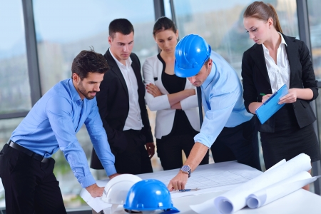 construction work: business people group on meeting and presentation  in bright modern office with construction engineer architect and worker looking building model and blueprint  plans