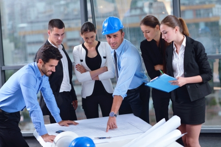 life partner: business people group on meeting and presentation  in bright modern office with construction engineer architect and worker looking building model and blueprint  plans