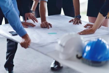 ingeniero: grupo de hombres de negocios en el cumplimiento y la presentaci�n en la luminosa oficina moderna con la construcci�n del arquitecto ingeniero y modelo de construcci�n trabajador en busca y planes detallados