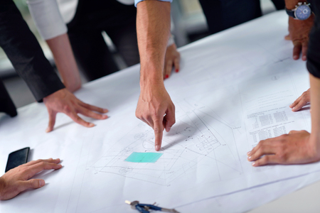 team working together: business people group on meeting and presentation  in bright modern office with construction engineer architect and worker looking building model and blueprint  plans