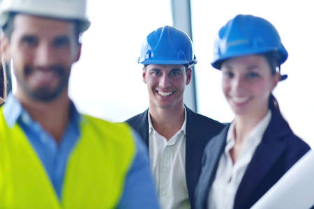 business people group on meeting and presentation  in bright modern office with construction engineer architect and worker looking building model and blueprint  plans photo