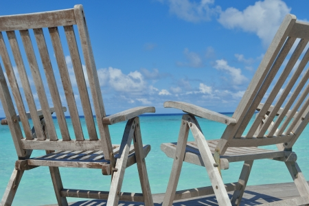 getaways: Two chairs beds in forest  on tropical beach with blue ocean in background