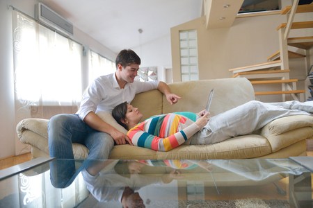 pregnant woman with her husband have fun relax and using tablet comture at modern home Stock Photo - 25075999