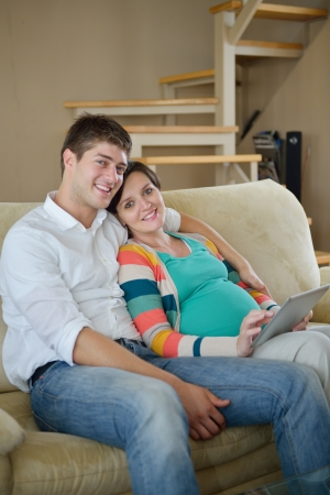 pregnant woman with her husband have fun relax and using tablet comture at modern home photo