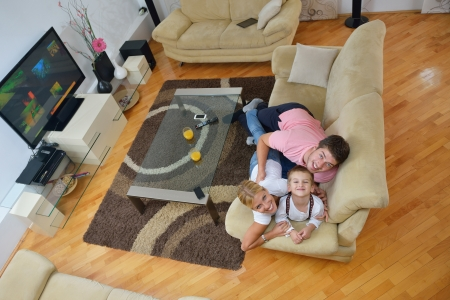happy young family with kids in bright modern living room have fun and looking big flat lcd tv Stock Photo - 25377591