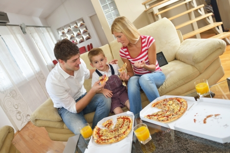 dring: happy young family eating tasty pizza with cheesa and dring healthy and fresh orange juice Stock Photo