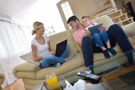 family couch: happy young family using tablet computer at modern  home for playing games and education