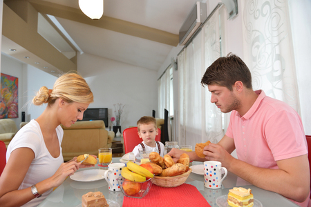 mums: happy young family have healthy breakfast at kitchen with red details on bright morning light