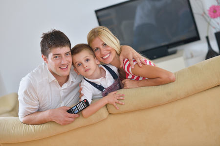 lcd tv: happy young family with kids in bright modern living room have fun and looking big flat lcd tv Stock Photo