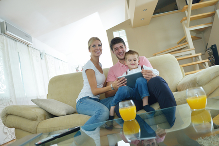 happy young family using tablet computer at modern  home for playing games and education photo