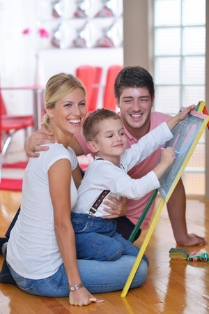 schooltime: happy young family teach leassons and prepare their son for school while draw on board at home