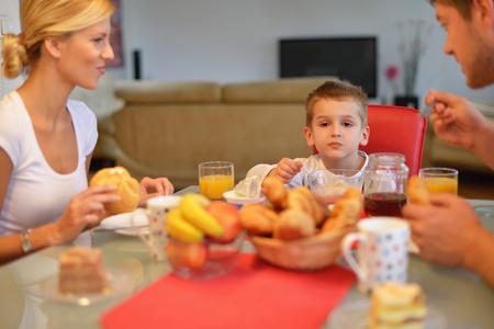 familia comiendo: familia joven feliz desayuno saludable en la cocina con detalles de color rojo en la luz brillante de la mañana