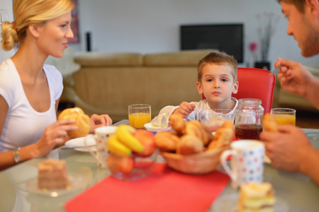 family eating: happy young family have healthy breakfast at kitchen with red details on bright morning light