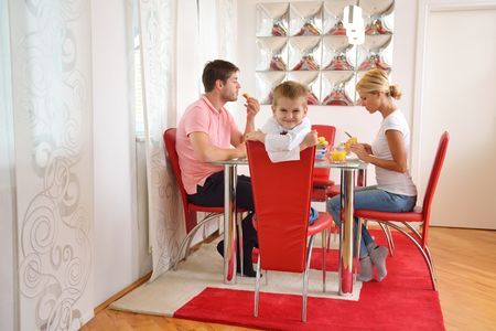niños desayunando: familia joven feliz desayuno saludable en la cocina con detalles de color rojo en la luz brillante de la mañana