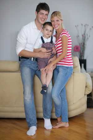 happy young family with kids in bright modern living room have fun and looking big flat lcd tv Stock Photo - 25257390