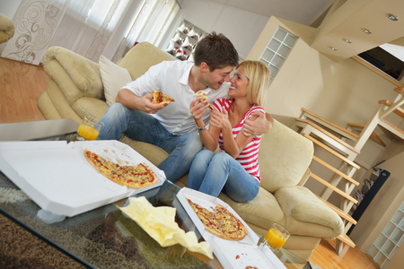 lifestyle dining: happy young couple eat fresh pizza at home relaxing and watch tv