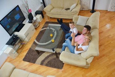 living together: happy young family with kids in bright modern living room have fun and looking big flat lcd tv Stock Photo