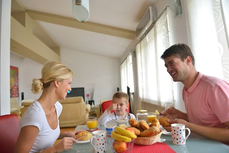 light breakfast: happy young family have healthy breakfast at kitchen with red details on bright morning light