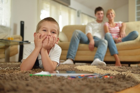 a big family: happy young family with kids in bright modern living room have fun and looking big flat lcd tv Stock Photo