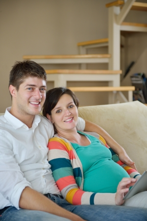 pregnant woman with her husband have fun relax and using tablet comture at modern home Stock Photo - 25288780