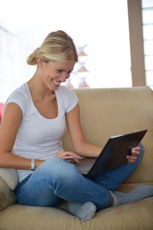 working at home: feliz mujer rubia joven en su casa trabajando en la computadora port�til Foto de archivo