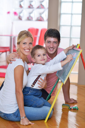 happy young family teach leassons and prepare their son for school while draw on board at home photo