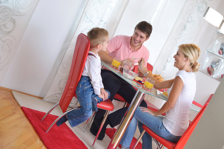 happy young family have healthy breakfast at kitchen with red details on bright morning light photo