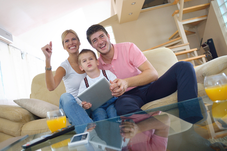 happy young family using tablet computer at modern  home for playing games and education Stock Photo - 25378219
