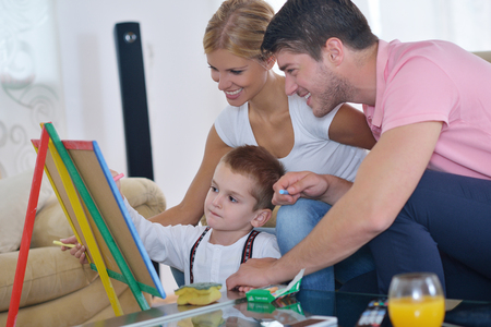 happy young family teach leassons and prepare their son for school while draw on board at home Stock Photo - 25378221