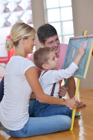 happy young family teach leassons and prepare their son for school while draw on board at home Stock Photo - 25378222