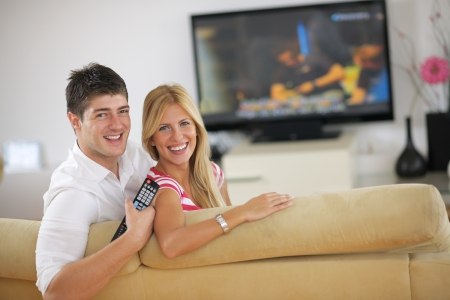 family sofa: Relaxed young  couple watching tv at home in bright living room Stock Photo