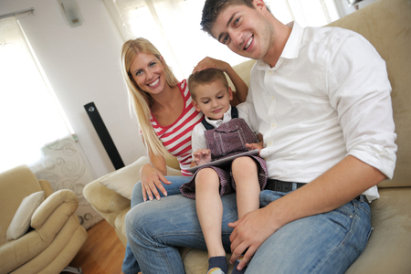 happy young family using tablet computer at modern  home for playing games and education Stock Photo - 25378224