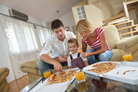 happy young family eating tasty pizza with cheesa and dring healthy and fresh orange juice photo