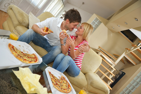 happy young couple eat fresh pizza at home relaxing and watch tv photo