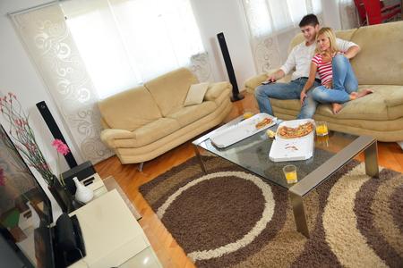 ver tv: joven pareja feliz comer pizza fresca en casa de relax y ver la televisión
