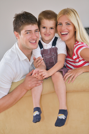 happy young family with kids in bright modern living room have fun and looking big flat lcd tv Stock Photo - 25289236