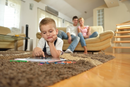 happy young family using tablet computer at modern  home for playing games and education