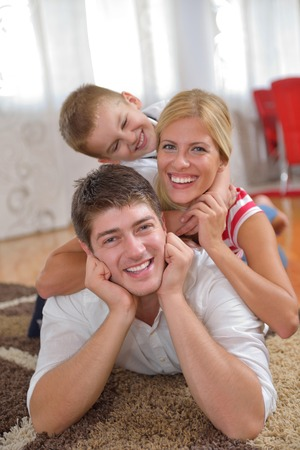 happy young family with kids in bright modern living room have fun and looking big flat lcd tv photo