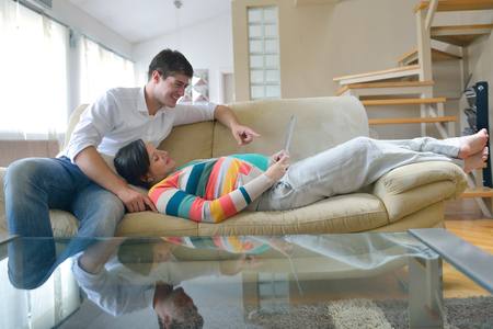pregnant woman with her husband have fun relax and using tablet comture at modern home Stock Photo - 25257241