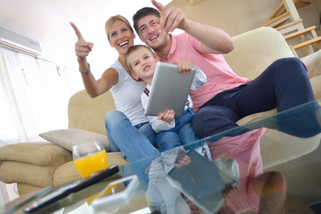 happy young family using tablet computer at modern  home for playing games and education Stock Photo - 25377976