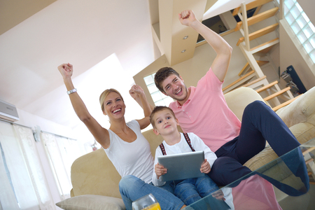 happy young family using tablet computer at modern  home for playing games and education Stock Photo - 25289296