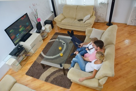 happy young family with kids in bright modern living room have fun and looking big flat lcd tv Stock Photo - 25289354
