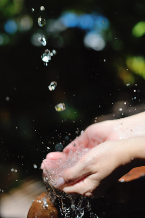 splashing fresh  water drops on girl soft skin  care for sensuality woman hands photo