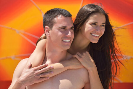 sun umbrella: happy young couple have fun and relax  on the beach