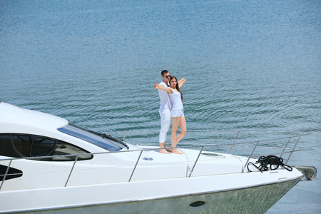 yacht people: Romantic young couple spending time together and relaxing on yacht