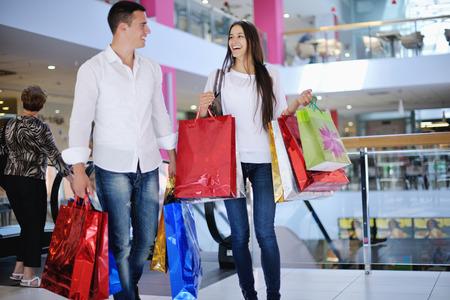 familia viaje: feliz pareja de jóvenes con bolsas en centro comercial centro comercial