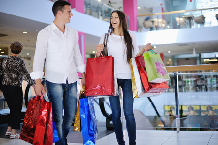 happy young couple with bags in shopping centre mall photo
