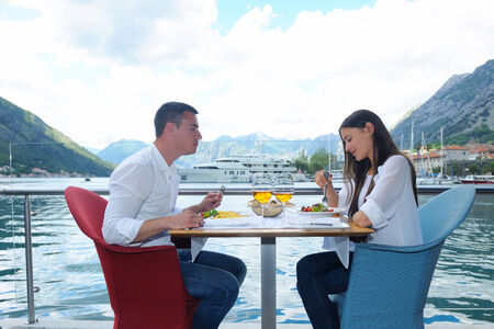 happy young couple having lanch at beautiful restaurant on the beach photo